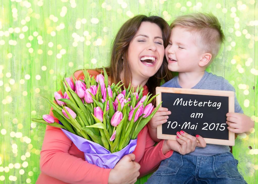 Mutter und Sohn auf einer grünen Wiese mit einem Blumenstrauß und Kreidetafel