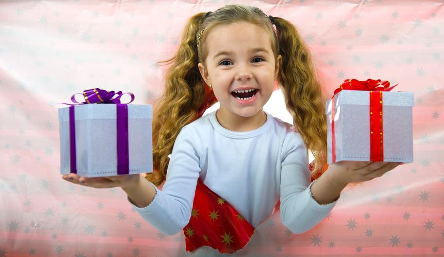 Ein Mädchen mit jeweils einer weißen Geschenkbox in einer Hand.