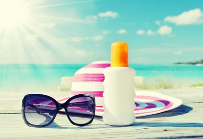 Sonnenbrille, Hut und Sonnencreme auf Holztisch