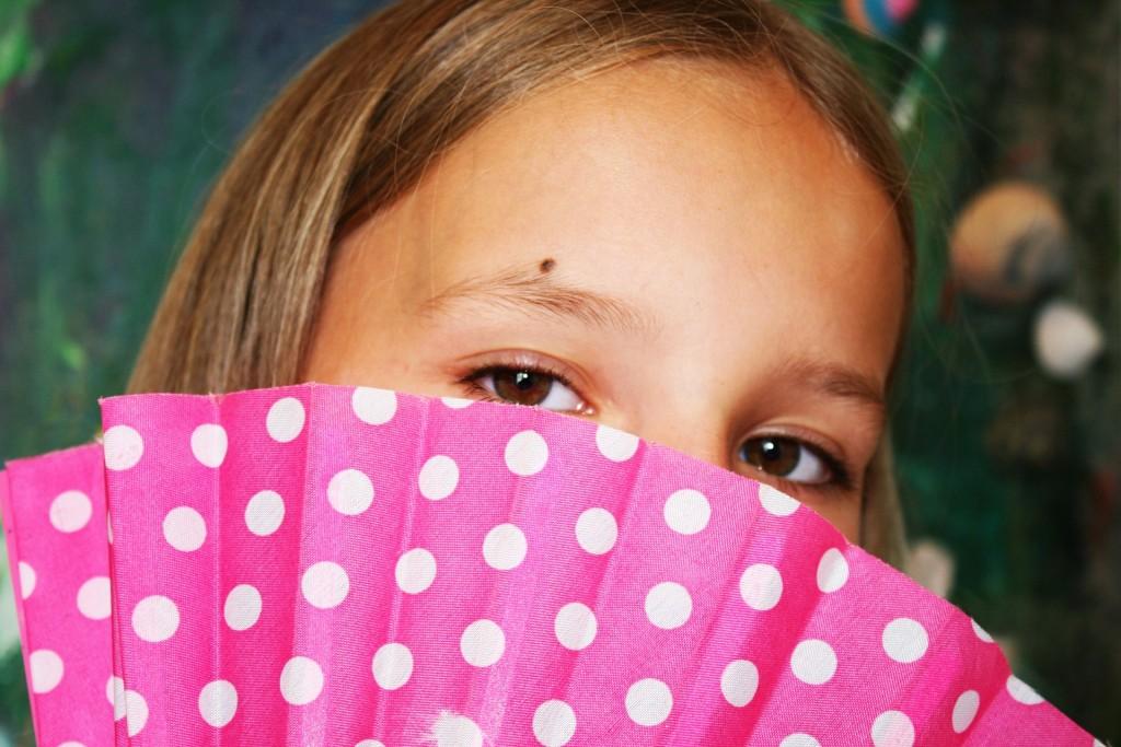 Mädchen mit Fächer vor dem Gesicht