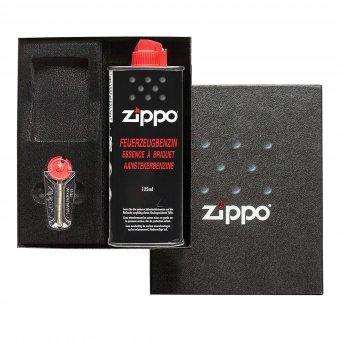 Zippo Box mit einer Flasche Benzin, Feuersteinen und einem Zippo, welcher mit einem Foto und Text graviert ist.