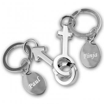 Zwei Schlüsselringe mit Mars und Venus Symbol. Jeweils ein ovales Gravurplättchen mit den Namen Finja und Paul.